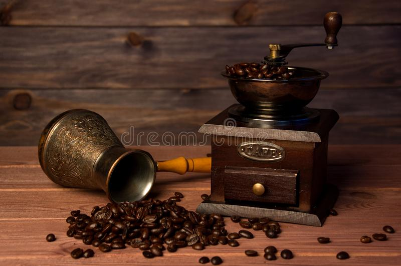 Vintage coffee grinder, turk copper coffee pot and coffee beans on brown wooden background. stock photography