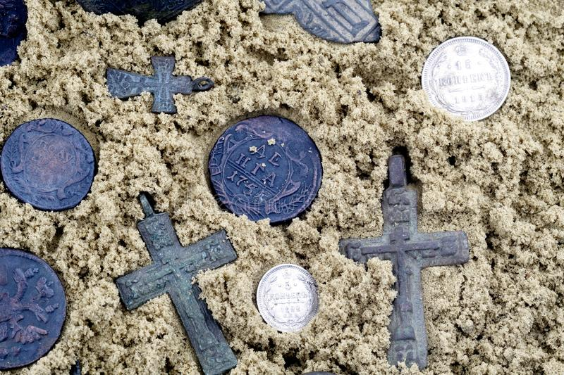 Vintage coins and crosses to wear around the neck. Background wet yellow sand royalty free stock photos