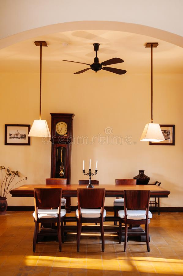 Vintage colonial dinner room with hard wood table, chairs and pedant lamps stock photos