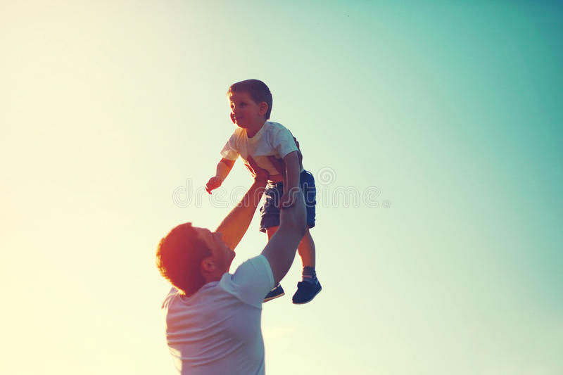 Vintage color photo happy joyful father throws up child. Vintage color photo happy joyful father having fun throws up in the air child, family, travel, vacation royalty free stock photography