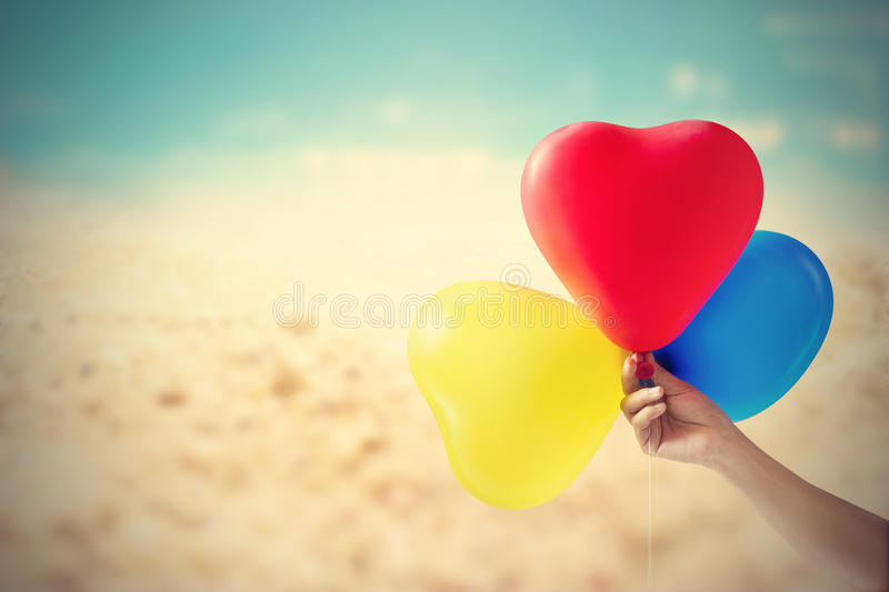 Vintage color tone balloon heart shape in hand on sea sand beach summer day and nature background. Soft focus stock photography