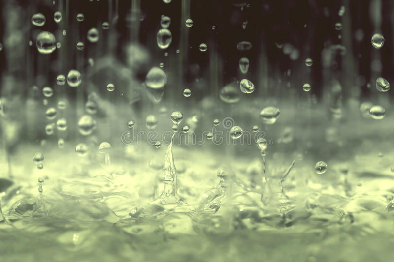 Vintage color tone of close up rain water drop falling to the floor in rainy season royalty free stock images