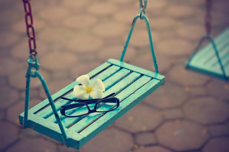 Vintage color tone style, glasses and white flower on the blue swing in evening stock images