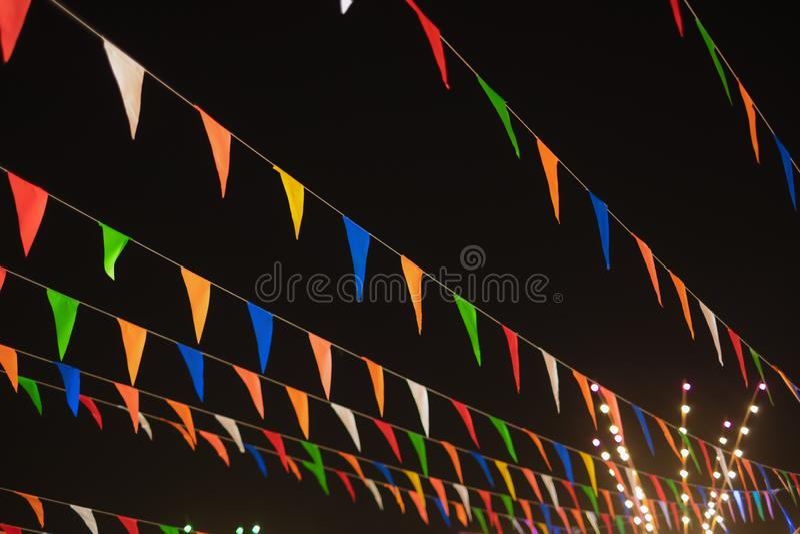 Vintage colorful flag banner ribbon on dark sky background in street carnival celebration. Abstract pattern of vintage colorful flag banner ribbon on dark sky stock image