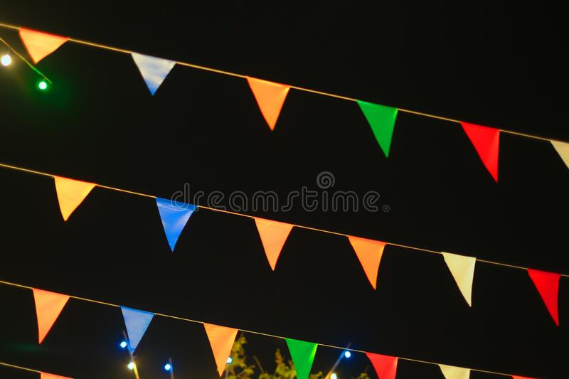 Vintage colorful flag banner ribbon on dark sky background in street carnival celebration for a happy holiday. Abstract pattern of vintage colorful flag banner stock image