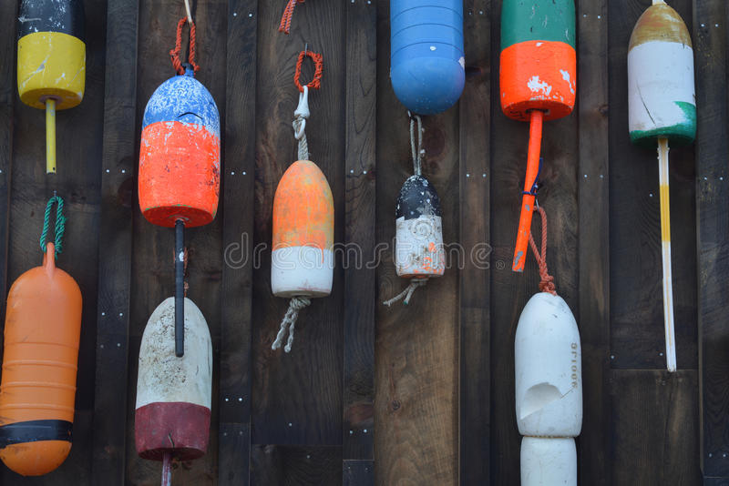 Vintage and colorful lobster floats hanging on an old Lobster fishing shack on the New England Coast. Of Maine royalty free stock images