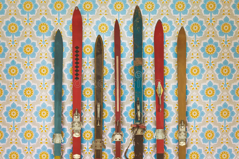 Vintage colorful used skis in front of retro wallpaper. Vintage colorful used skis in front of retro flower wallpaper stock image