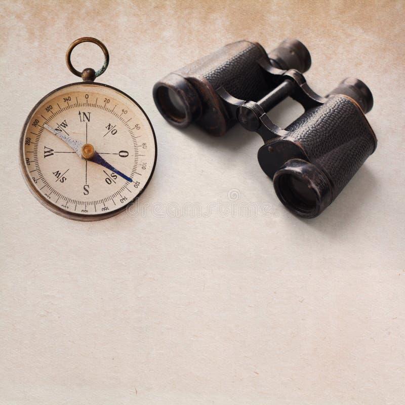 Vintage compass, aged binocular. manuscript background stock photography