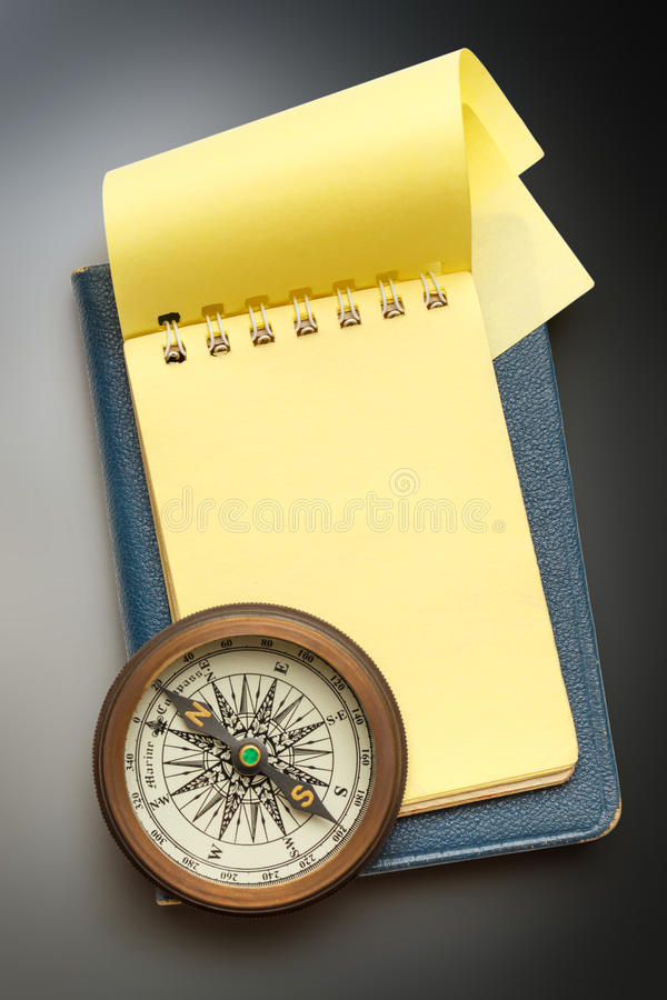 Vintage compass and blank yellow notepad royalty free stock image
