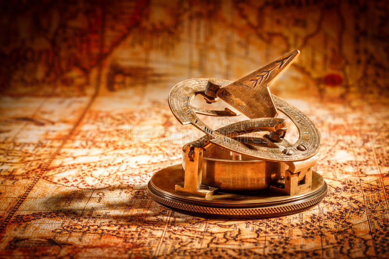 Vintage compass lies on an ancient world map. Vintage still life. Vintage compass lies on an ancient world map in 1565 stock photo