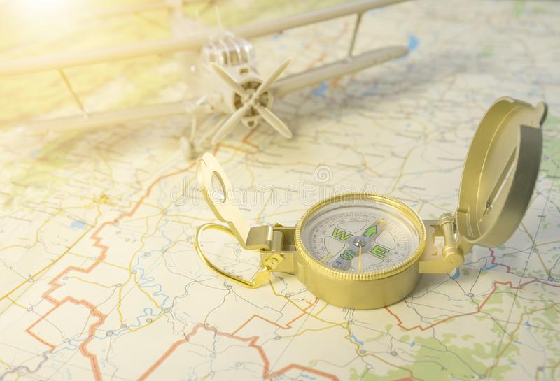 A vintage compass on the map and an airplane stock image