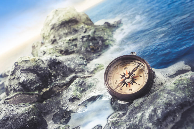 Vintage compass on the sea shore stock photography