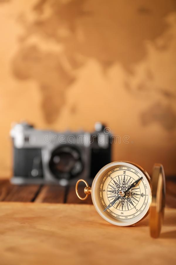 Vintage compass with sheet of paper on table against blurred background stock photography