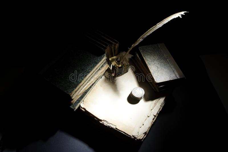 Vintage concept. Old fountain pen, papers and inkwell and silver coins on a black background royalty free stock photos