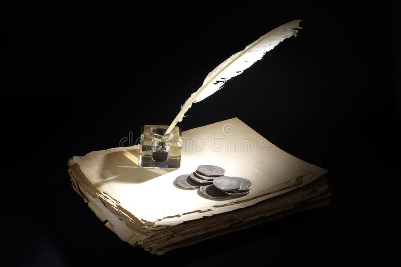 Vintage concept. Old fountain pen, papers and inkwell and silver coins on a black. Background stock photography