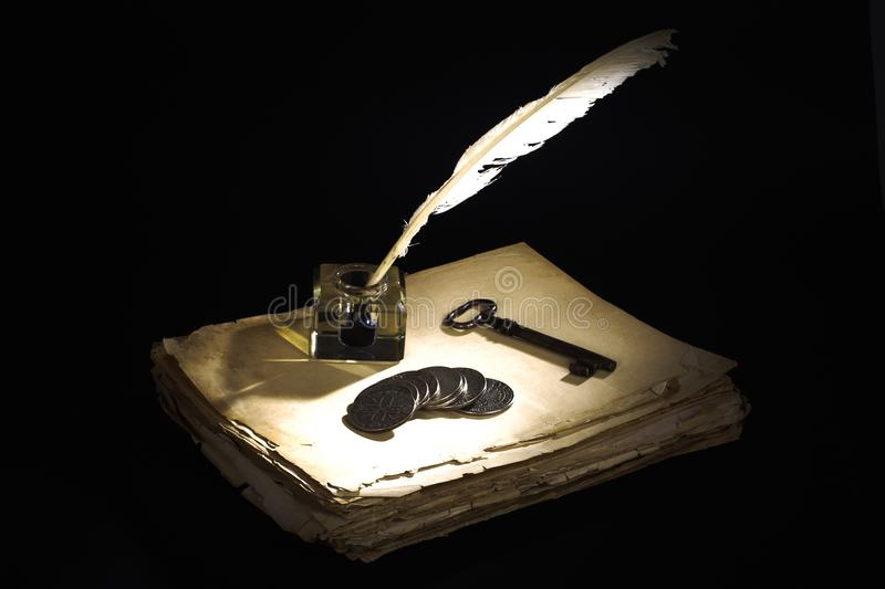 Vintage concept. Old fountain pen, papers and inkwell and silver coins on a black. Background stock images