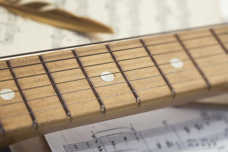 conceptual composition of notes, wooden guitar and sound board a golden bird`s feather is on a sheet of old yellowed and royalty free stock photos