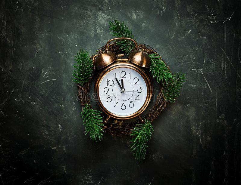 Vintage copper Alarm Clock Five Minutes to Midnight New Years Countdown Christmas Wreath Fir Tree Branches on Black Background stock photography