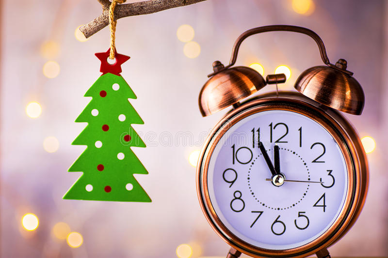 Vintage copper alarm clock showing five minutes to midnight, New Year countdown. Green christmas tree ornament hanging on branch stock images