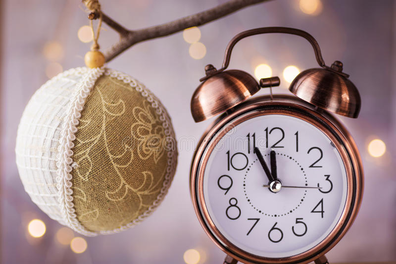 Vintage copper alarm clock showing five minutes to midnight, New Year countdown. Handmade linen fabric lace ball ornament hanging royalty free stock image