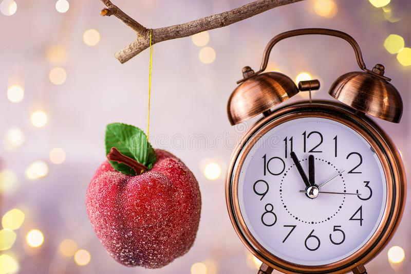Vintage copper alarm clock showing five minutes to midnight. New Year countdown. Sugar coated red apple ornament hanging on branch stock images