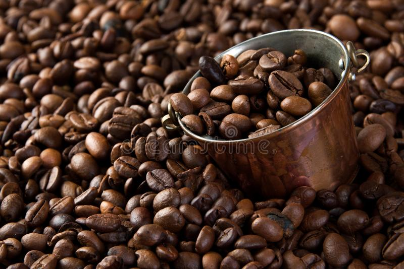Vintage copper bucket on coffee beans background. Copy space for text royalty free stock images