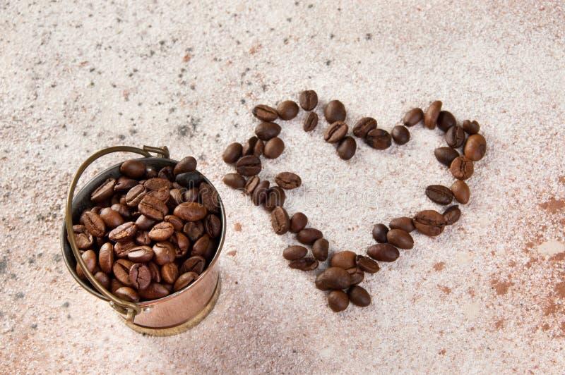 Vintage copper bucket on concrete background. Vintage copper bucket full of coffee beans and shape of the heart from coffee beans on concrete background. Copy stock images