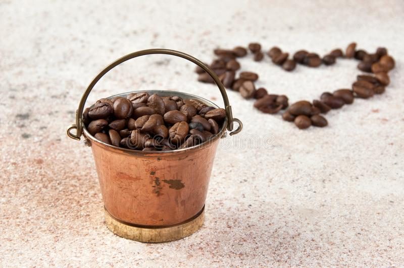 Vintage copper bucket on concrete background. Vintage copper bucket full of coffee beans and shape of the heart from coffee beans on concrete background. Copy royalty free stock photography