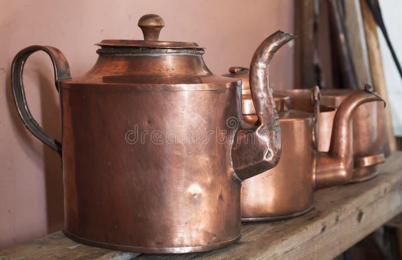 Vintage copper teapots stand on shelf stock photos
