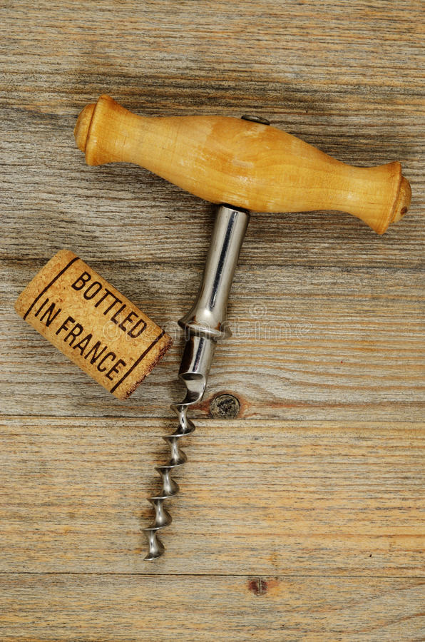 Vintage corkscrew and wine cork with inscription bottled in Fran. Vintage old corkscrew and wine cork with inscription bottled in France stock image