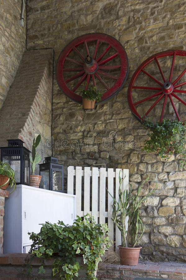 Vintage corner in an old style restaurant. In Tuscany, Italy, with red wheels hung on the wall stock photo