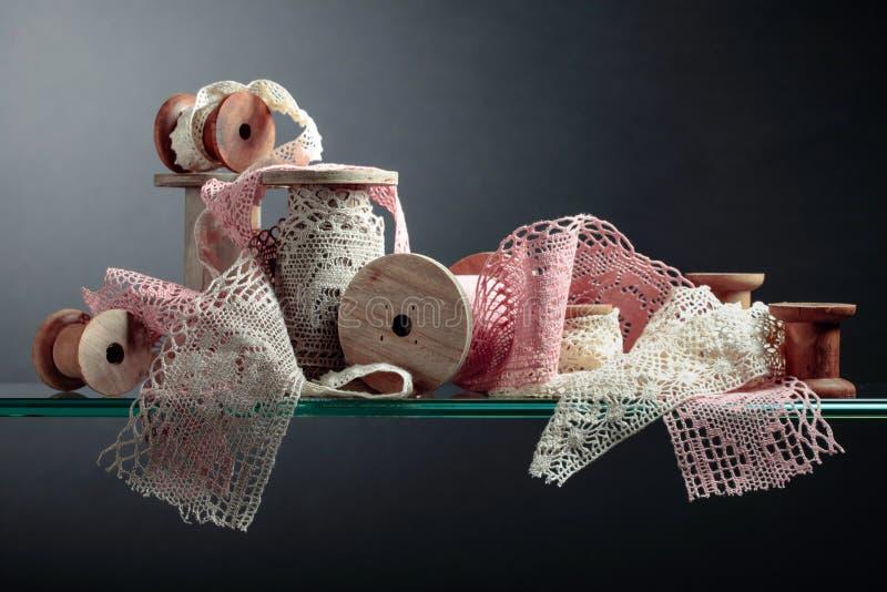 Vintage cotton lace trims on wooden spools stock photo