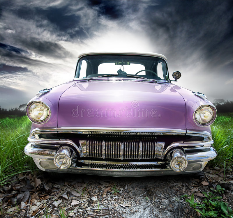 Vintage coupe. A two door lavender convertible vintage American automobile with white walled tires. Dice hanging from mirror show seven. Front view of a