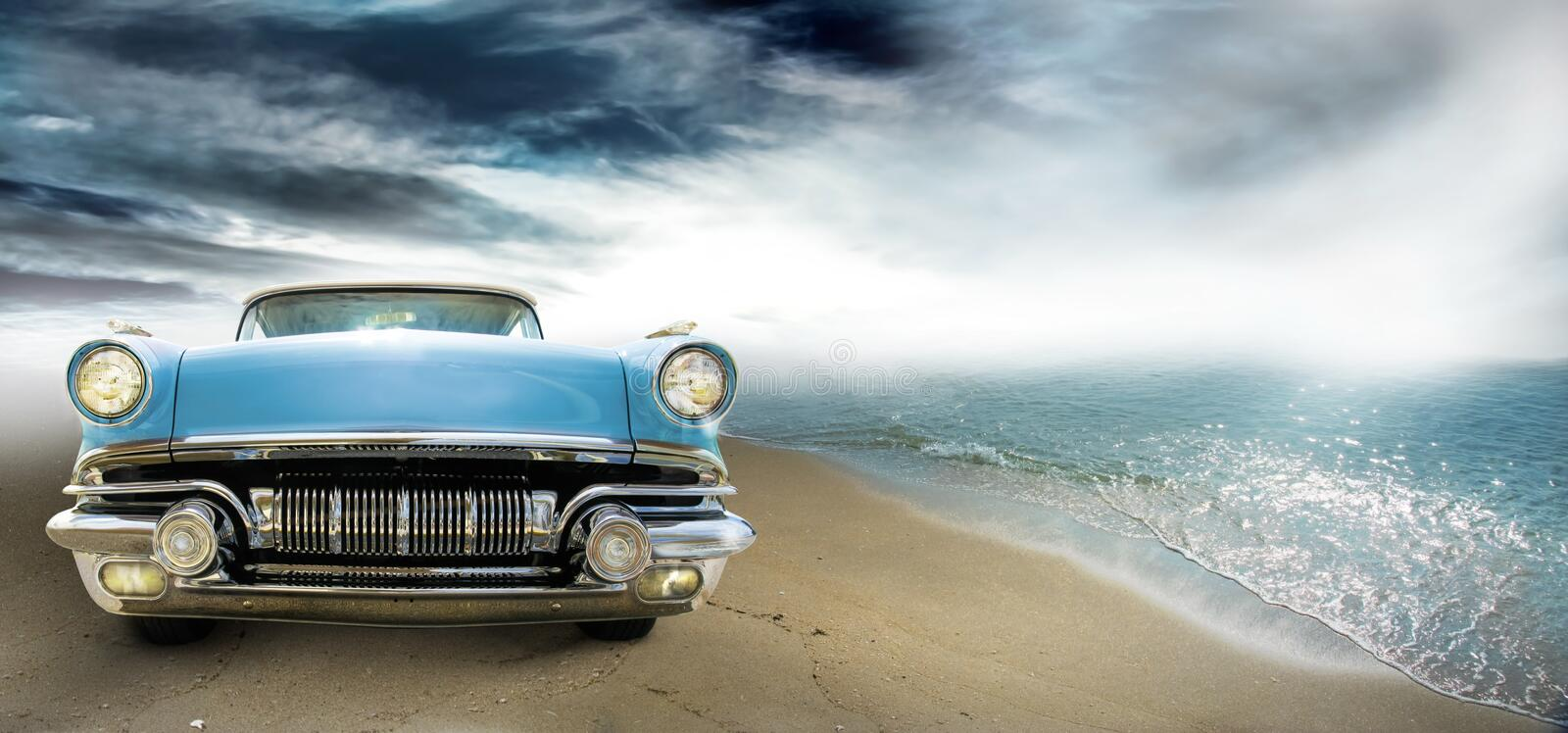Vintage coupe. A two door cyan convertible vintage American automobile on a sandy beach with stormy background. Front view of a collectible Pontiac Sky Chief