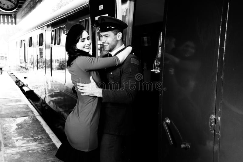 Vintage couple embracing and laughing on railway station platform as train arrives stock image