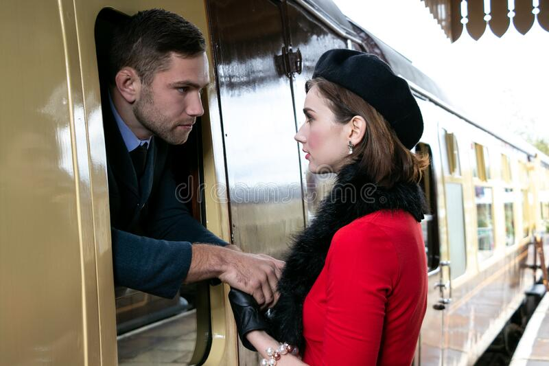 Vintage couple, man in uniform, woman in red dress, holding hands goodbye at train station as train departs royalty free stock photo