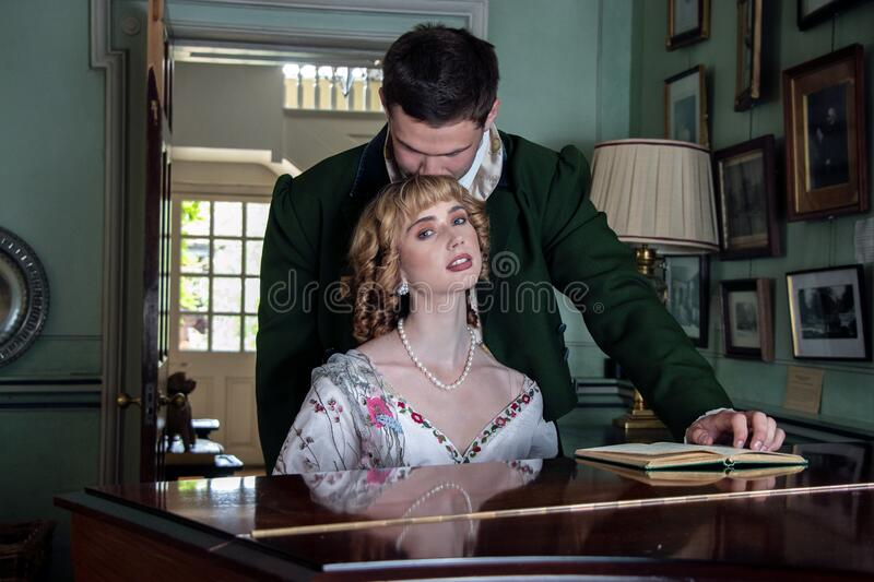 Vintage couple in period costume sitting around piano playing tunes with man kissing woman in the head royalty free stock images