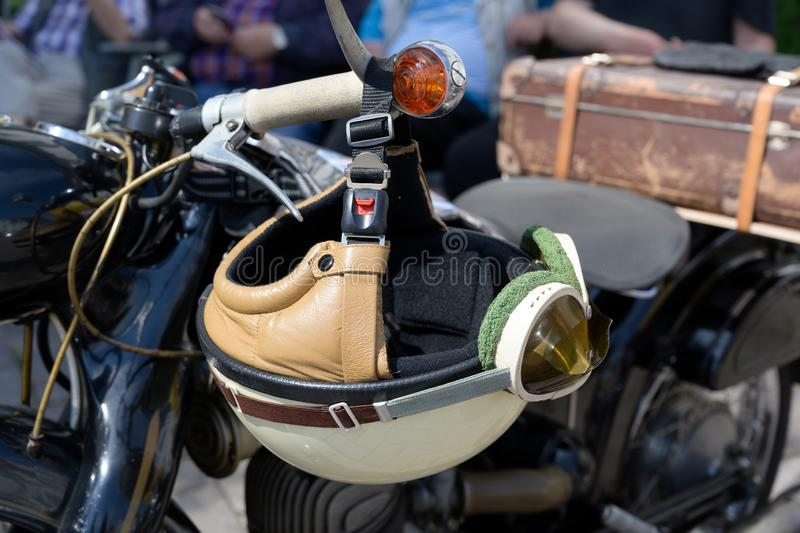 Vintage crash helmet is hanging on the handlebar of a classic oldtimer motorbike royalty free stock photography