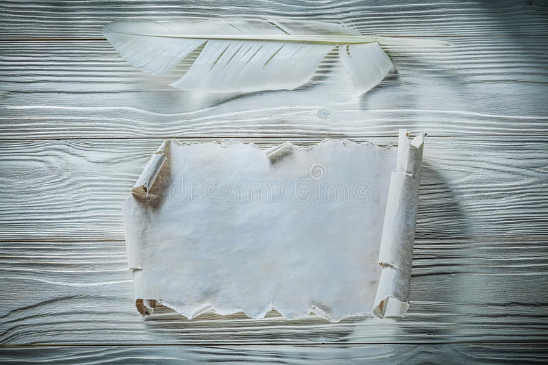 Vintage crumpled paper roll quill on wooden board.  royalty free stock image