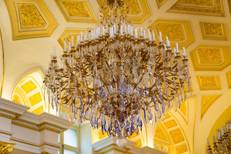 Vintage crystal chandelier view from below against the painted ceiling. Moscow attractions royalty free stock photos