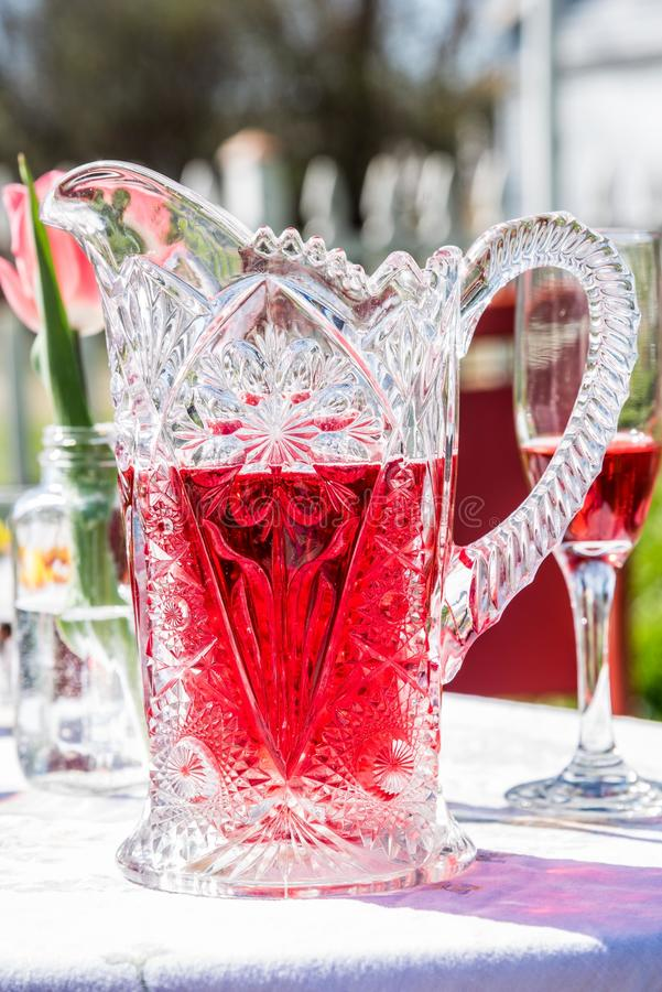 Vintage crystal pitcher of refreshing cranberry champagne in sunlight stock photos