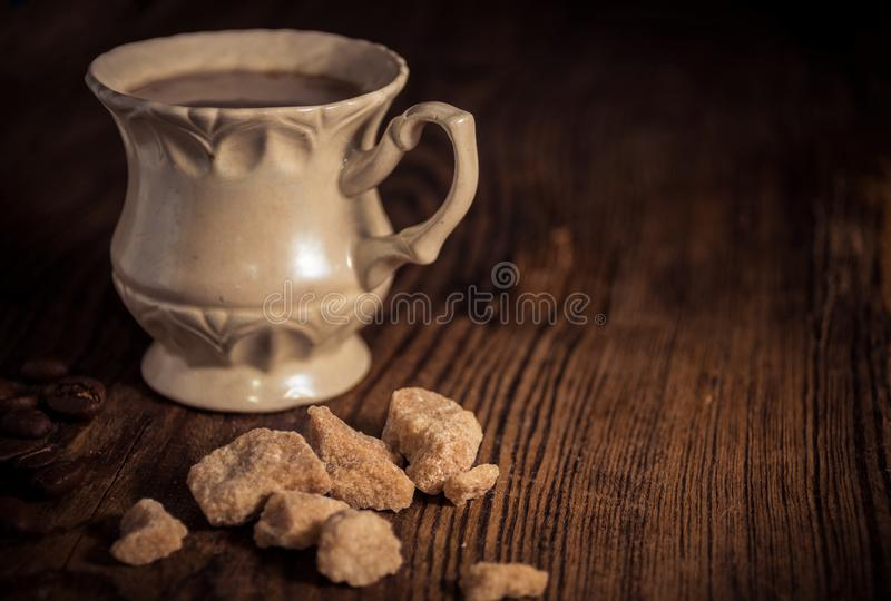 Vintage cup of coffee with pieces of brown sugar and coffee beans royalty free stock image