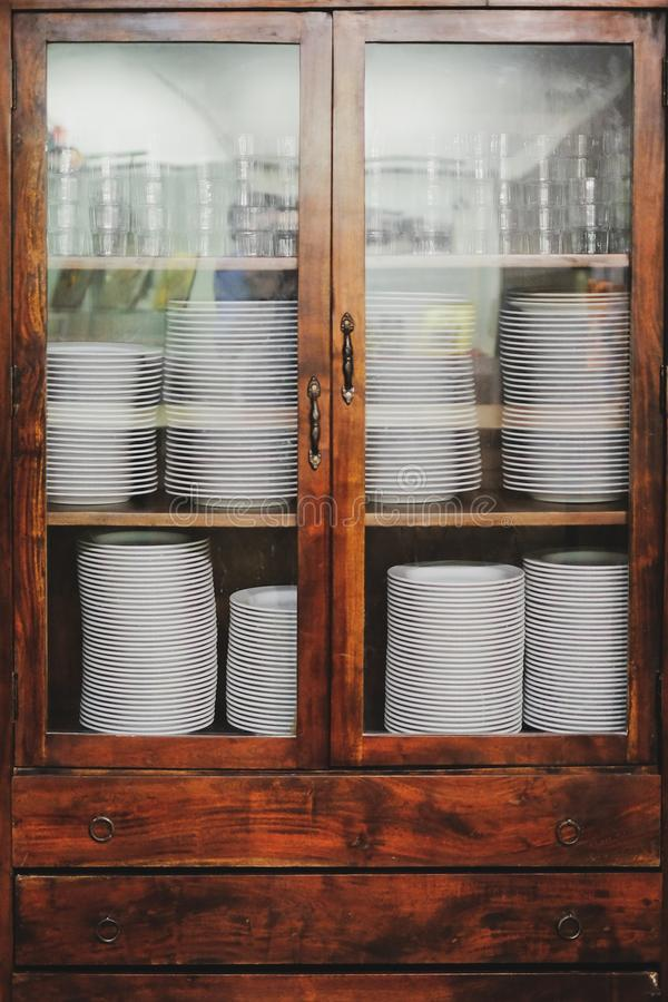 Vintage cupboard with dinnerware. old wooden kitchen cabinet with stack of white plates and cups. retro sideboard. Vintage cupboard with white dinnerware. old stock photo