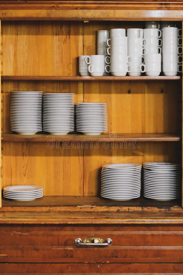 Vintage cupboard with dinnerware. old wooden kitchen cabinet with stack of white plates and cups. retro sideboard. Vintage cupboard with white dinnerware. old stock photos