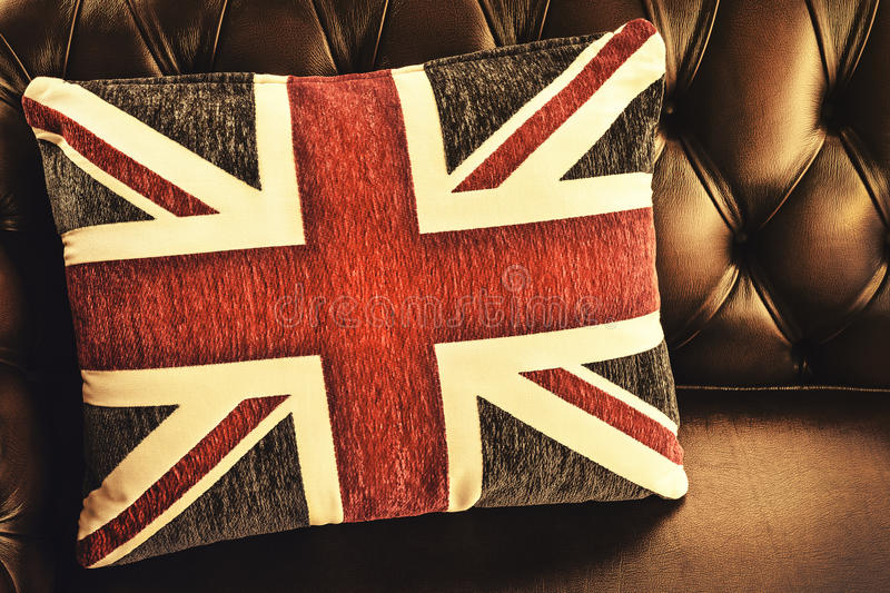 Vintage cushion with the English flag on a sofa. Retro styled image of a cushion with the English flag on a chesterfield sofa royalty free stock images