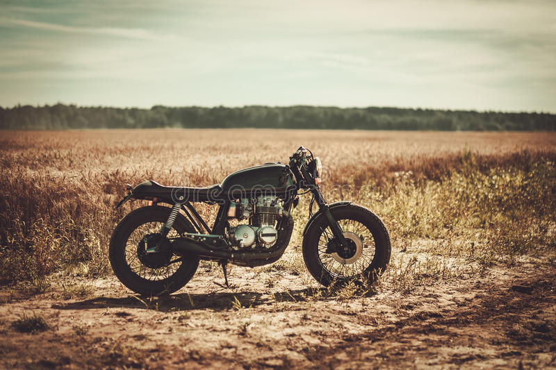 The vintage custom cafe racer in a field.  stock photos