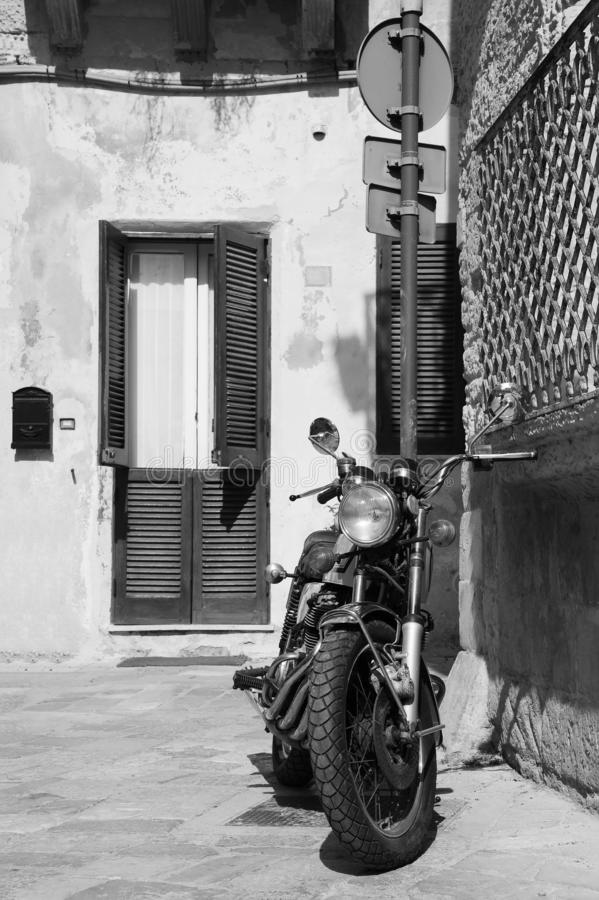 Vintage custom motorcycle standing in the street  of old italian town. Lecce, Apulia, Italy. Vintage custom motorcycle standing in the street of old italian town stock photography