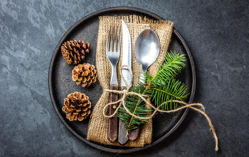 Vintage cutlery set, Christmas decoration on iron plate, slate background. Vintage rustic cutlery set with country style napkin and Christmas decoration - fir royalty free stock images