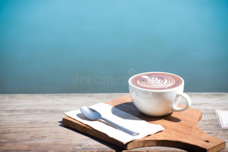 Vintage da arte quente do cappuccino do copo de café, colher, tecido, placa de desbastamento na tabela de madeira com espaço da c foto de stock