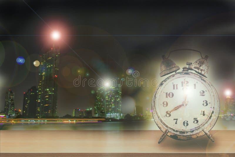 Vintage da exposição dobro do despertador retro na tabela de madeira no fundo da cidade da noite imagens de stock royalty free